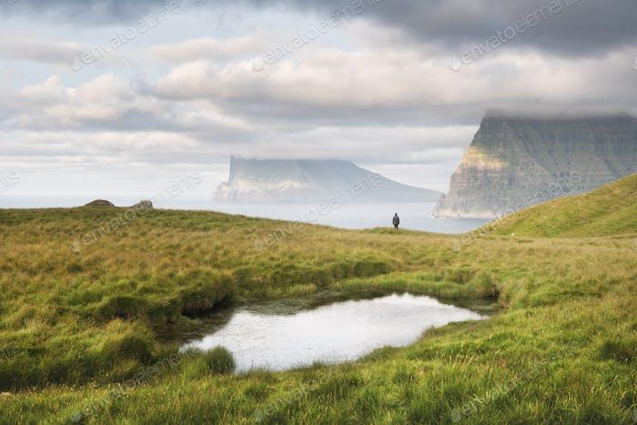 Einsamer Tourist in der Nähe des kleinen Sees blickt auf neblige Inseln im Atlantischen Ozean