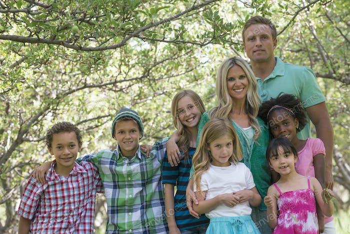 Um grande grupo de crianças e dois adultos. Amigos e famílias ao ar livre juntos.