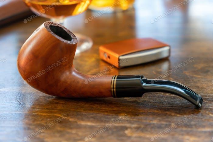 Smoking pipe on wooden office desk. Tobacco smoking habit