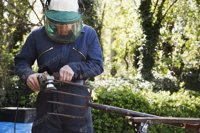 Man standing outdoors, wearing a face mask, working on a large metal garden fork or pitchfork with