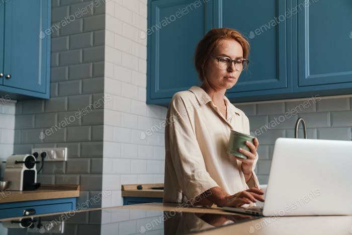 Image of drinking ginger woman drinking coffee and using laptop