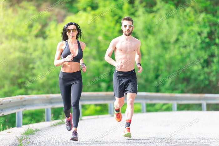 Woman with sports body during a race and personal trainer