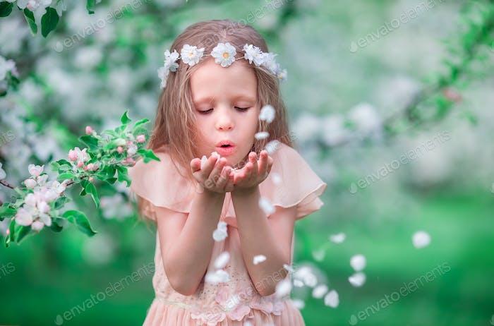Portrait of adorable little girl in blooming cherry tree garden outdoors