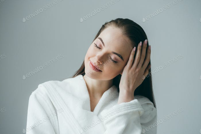 Eine Frau in einem weißen Mantel berührt ihr Haar. Das Konzept der Spa-Kosmetik.