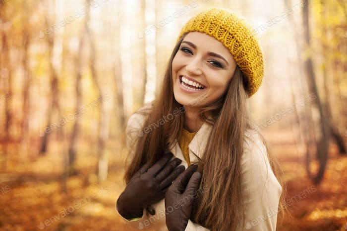 Young woman wearing autumn clothes laughing in park
