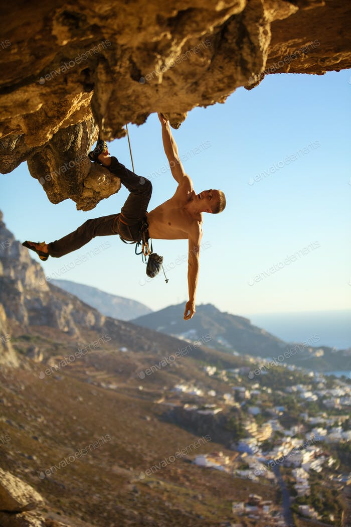 Young man climbing on roof of cave against picturesque view of coast