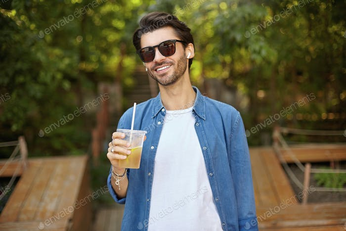 Portrait of lovely bearded male in sunglasses posing over public outdoor place, looking at camera