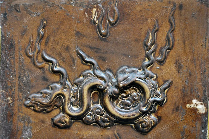 Bas relief, carved brass detail on a bronze backgrounf