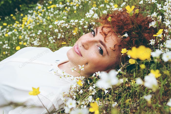Young redhead woman in a field of flowers