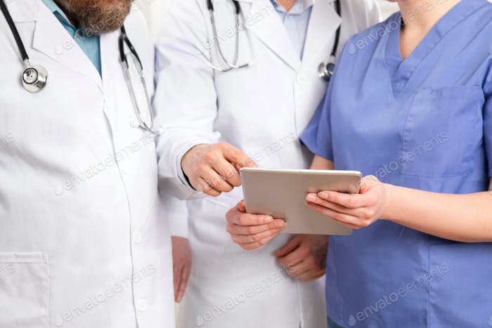 Doctor in medical team discussing patient report at tablet computer in hospital