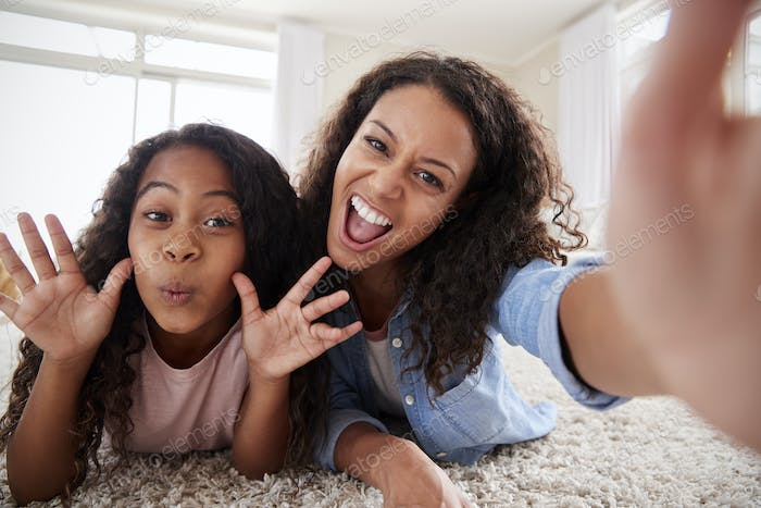 Mother And Daughter Lying On Rug And Posing For Selfie At Home