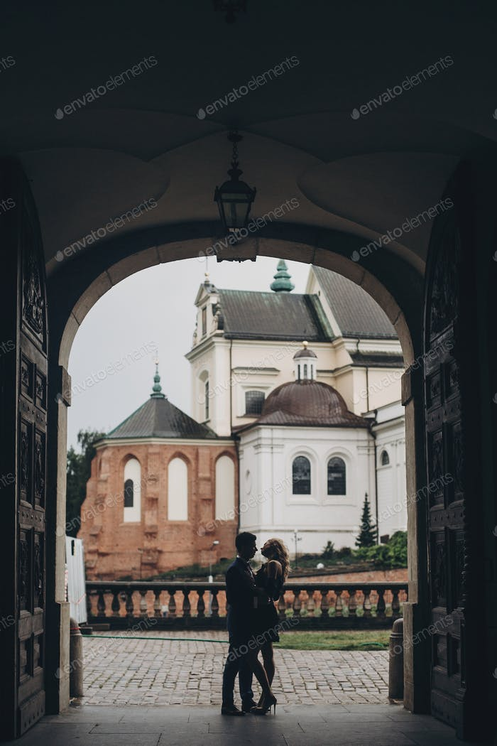 Couple embracing in european city street on background of old architecture