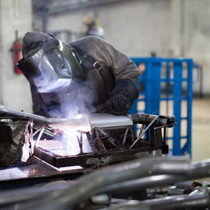 worker welding exhaust pipes pieces together