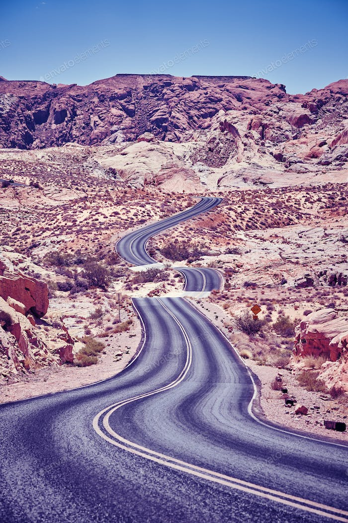Vintage toned picture of a winding desert road.