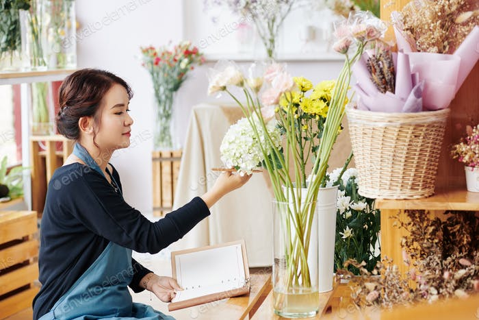 Florist checking flowers and taking notes