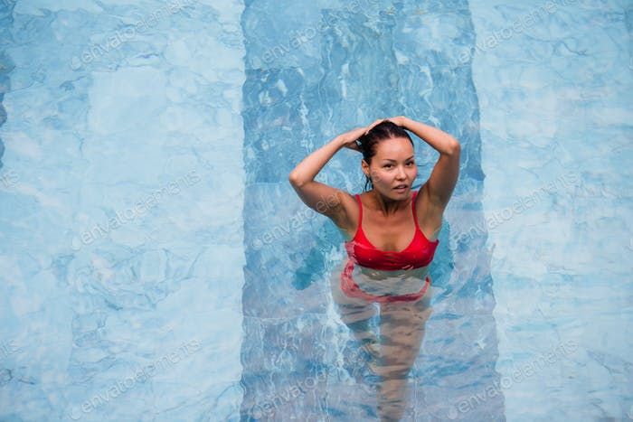 Top view of a beautiful sexy adult asian woman in the swimming pool