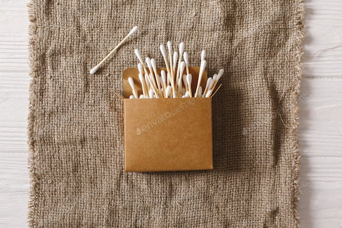 Eco natural bamboo ear sticks flat lay on rustic background