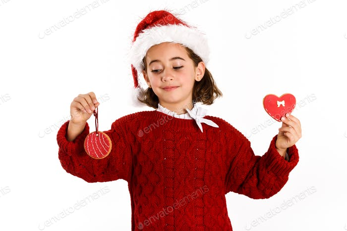 Adorable little girl wearing santa hat with Christmas biscuits
