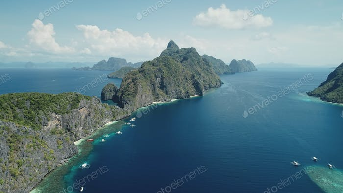 Mountain islet at tropic sea aerial view. Panoramic shot of green jungle at mount at sunny weather