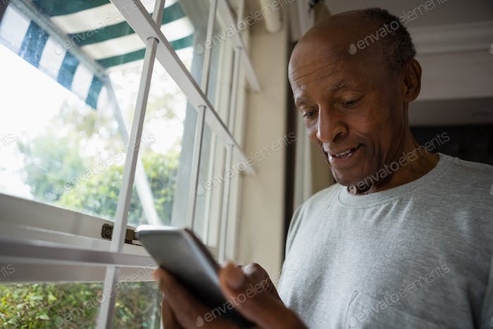 Senior man using mobile phone by window