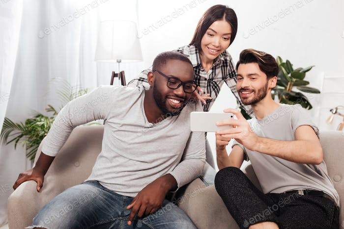 Portrait of three smiling friends sitting on chairs at home and joyfully using mobile phone