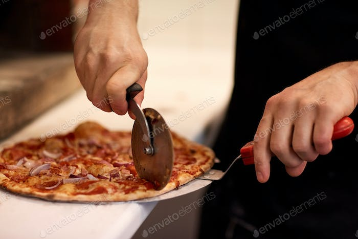 cook hands cutting pizza to pieces at pizzeria