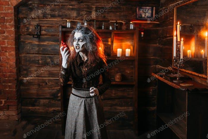 Gruselige Hexe hält menschliches Herz am Spiegel