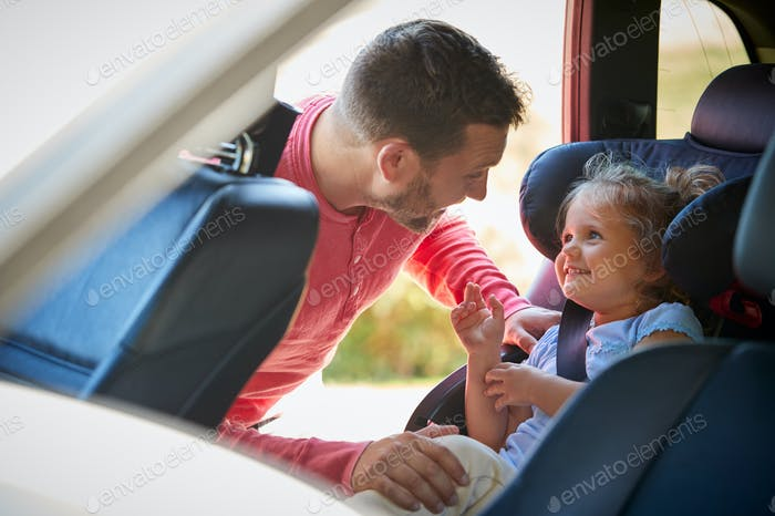 Father Securing Daughter Into Rear Child Seat Before Car Journey