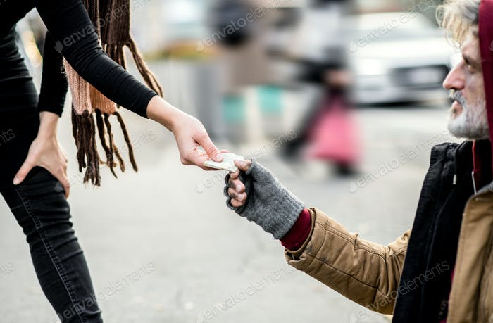 A midsection of woman giving money to homeless beggar man sitting in city.