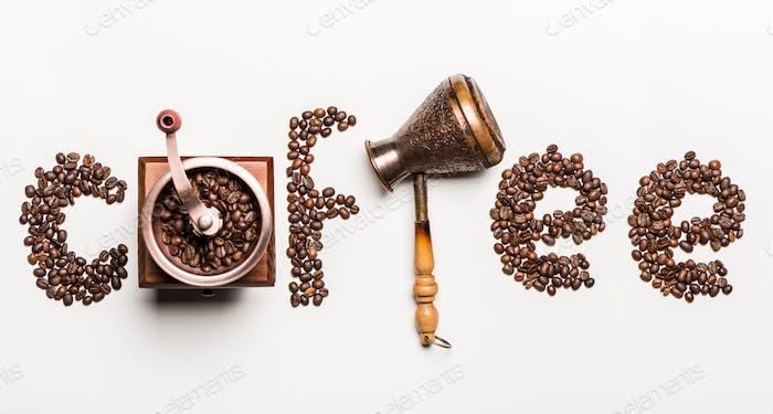 Vista superior del café palabra hecho de granos de café y molinillo de café con cafetera turca