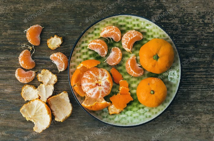 A plate of fresh ripe juicy mandarins over a rough wood backgrou