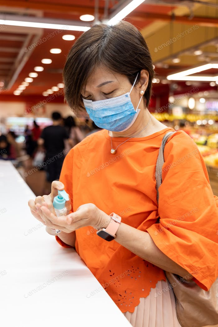 Asian woman applying sanitizer onto hand for protection against virus germs