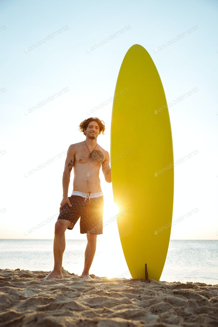 Smiling surfer holding surf board while standing at the beach