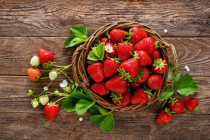 Strawberry in basket with twigs and leaves on rustic wooden table closeup