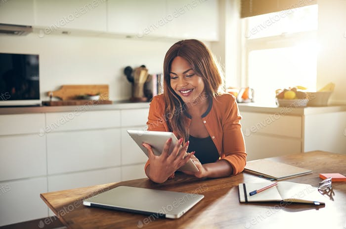 Smiling young female entrepreneur using a tablet in her kitchen