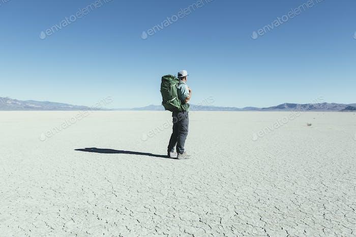 Male backpacker hiking in vast desert, Black Rock Desert, Nevada