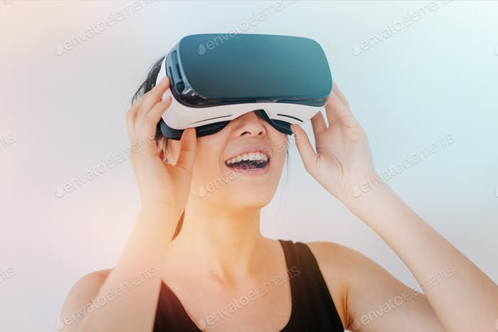 Smiling young woman using the VR goggles