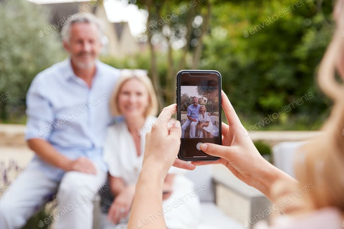 Adult Daughter Taking Picture Of Senior Parents Sitting In Garden On Mobile Phone