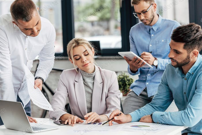 professional young businesswoman working with male colleagues in office