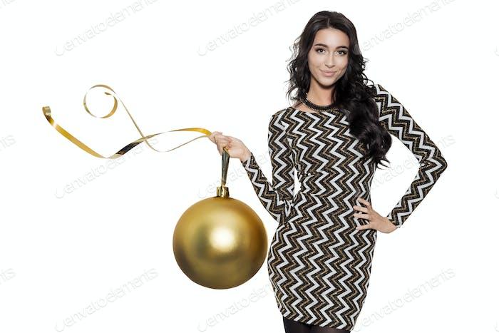 Charmante Frau hält große goldene Baumkugel. Frohes Neues Jahr.