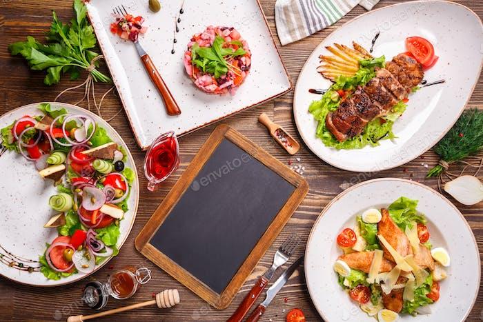 Diferentes ensaladas en mesa de De madera, vista superior.