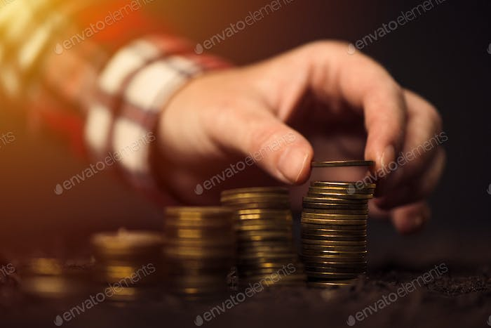 Farmer stacking coins, agricultural income