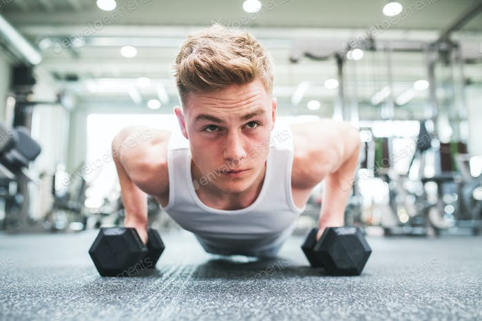 A close-up of young fit man in gym doing push ups on dumbbells.