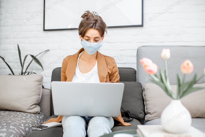 Woman in medical mask working from home
