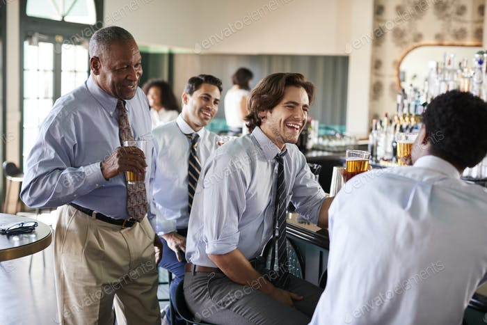 Group Of Businessmen Meeting For After Works Drinks In Bar