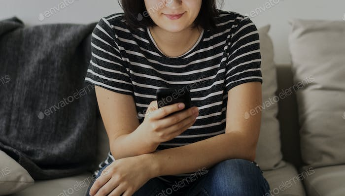 Woman sitting on a couch using smartphone