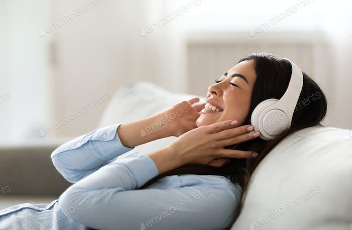 Lieblings-Freizeit. Entspannte afrikanische Mädchen Musik hören In drahtlosen Kopfhörern Mit geschlossenen Augen