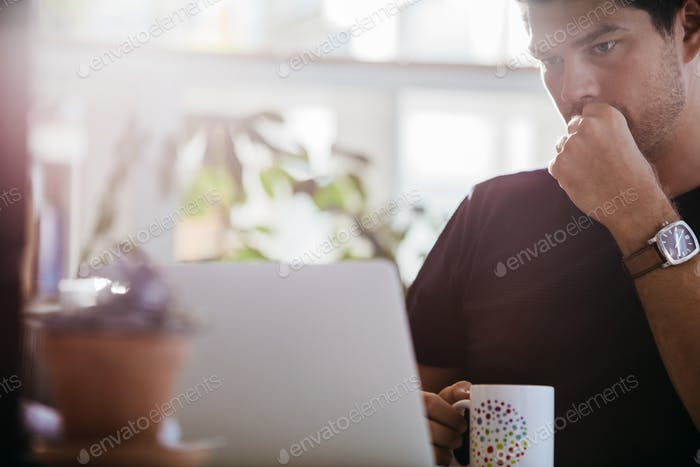 Serious male executive looking at laptop