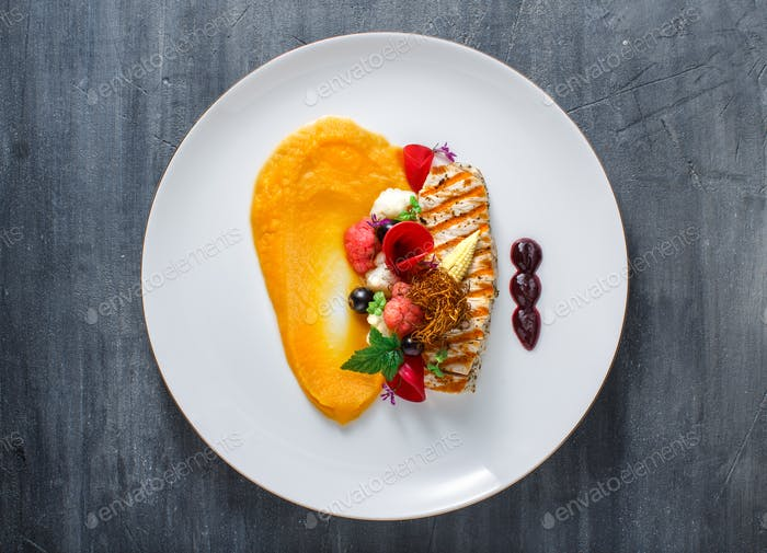Grilled turkey fillet with pumpkin puree and vegetables on white plate. Close view.