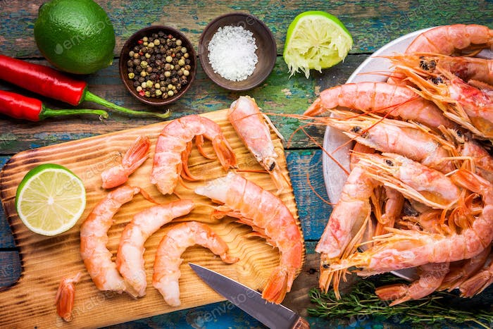 fresh shrimps on wooden board with salt, chili pepper, lime